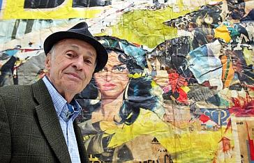 """Jacques Villeglé posant devant son oeuvre intitulée """"Rue de la Biche Saint-Denis"""" de 1963"""